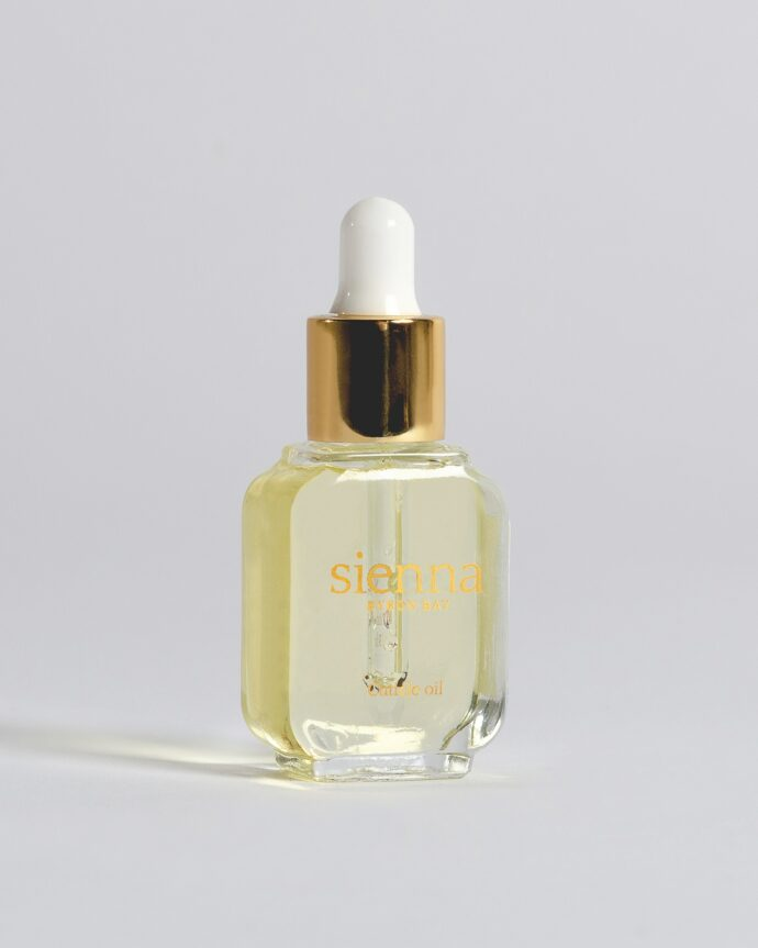 cuticle oil in glass bottle with gold dropper by sienna