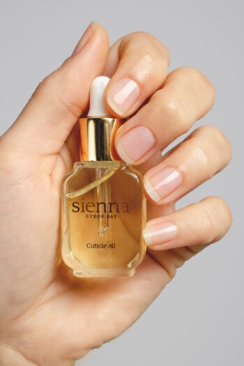 fair skin tone hand holding a bottle of cuticle oil by sienna