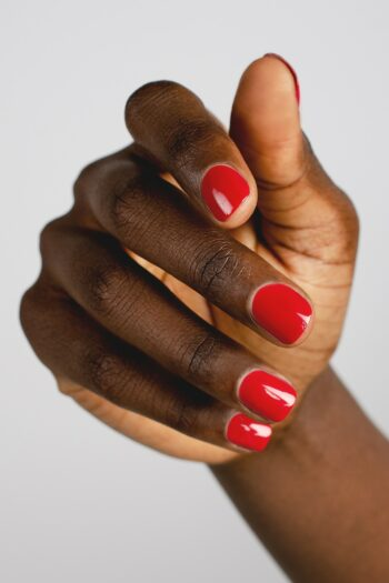 classic red nail polish hand swatch on dark skin tone by sienna