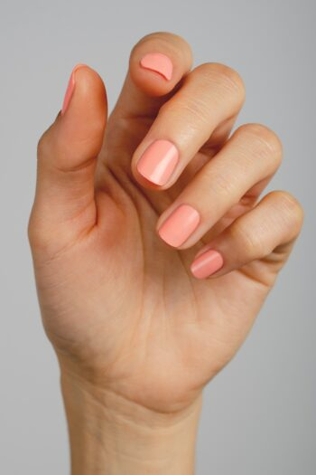 fluo peach nail polish hand swatch on fair skin tone by sienna
