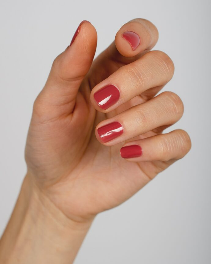 dusty red nail polish hand swatch on fair skin tone by sienna