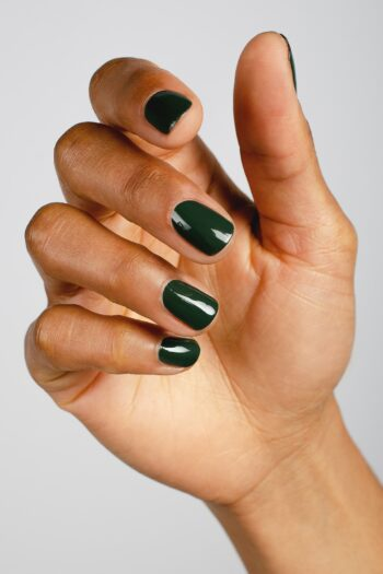 dark green nail polish hand swatch on medium skin tone by sienna