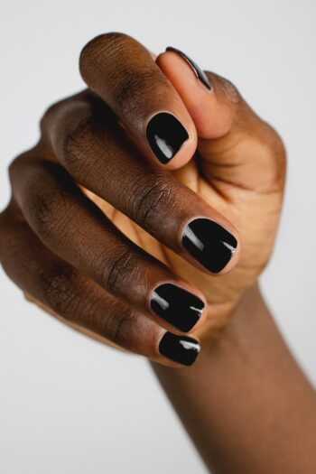 black nail polish hand swatch on dark skin tone by sienna