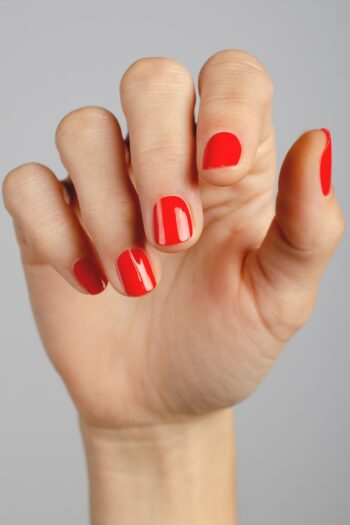 bright red nail polish hand swatch on fair skin tone by sienna