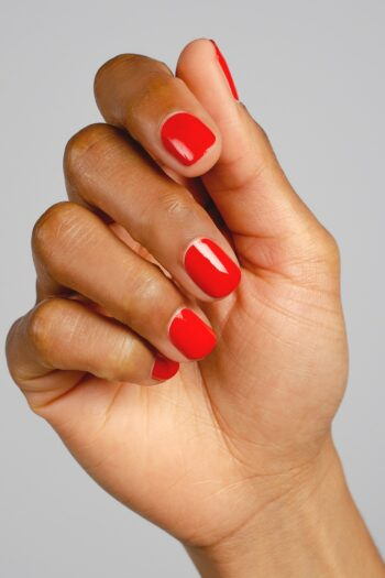 bright red nail polish hand swatch on medium skin tone by sienna