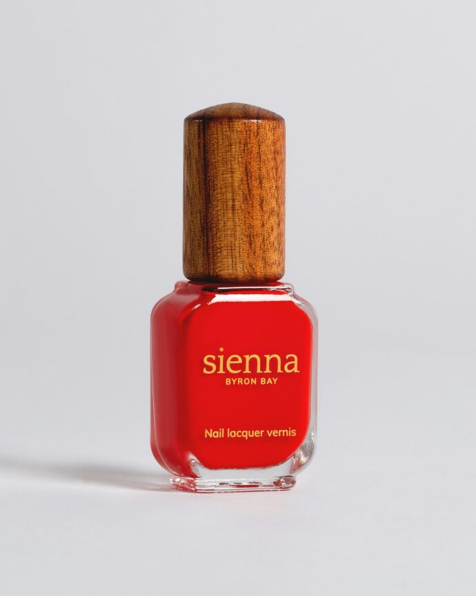 bright red nail polish bottle with timber cap by sienna