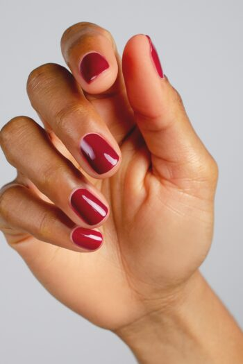 plum red nail polish hand swatch on medium skin tone by sienna