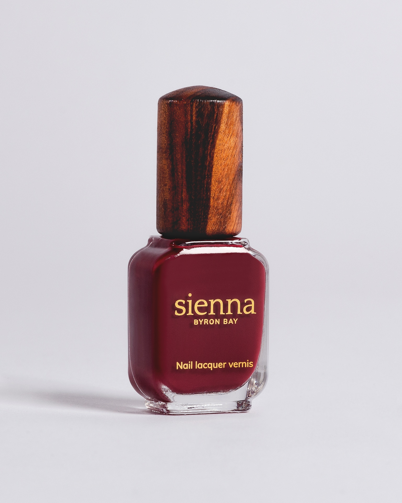 plum red nail polish bottle with timber cap by sienna