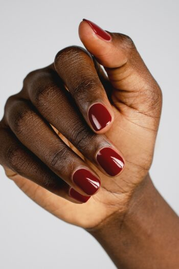 dark red nail polish hand swatch on dark skin tone by sienna