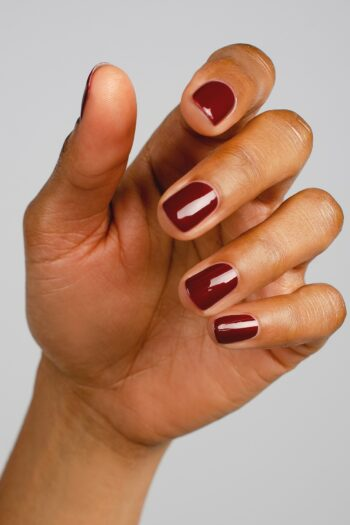 dark red nail polish hand swatch on medium skin tone by sienna