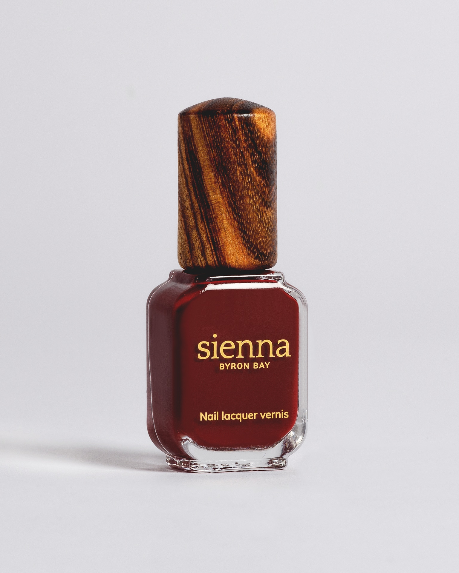 dark red nail polish bottle with timber cap by sienna