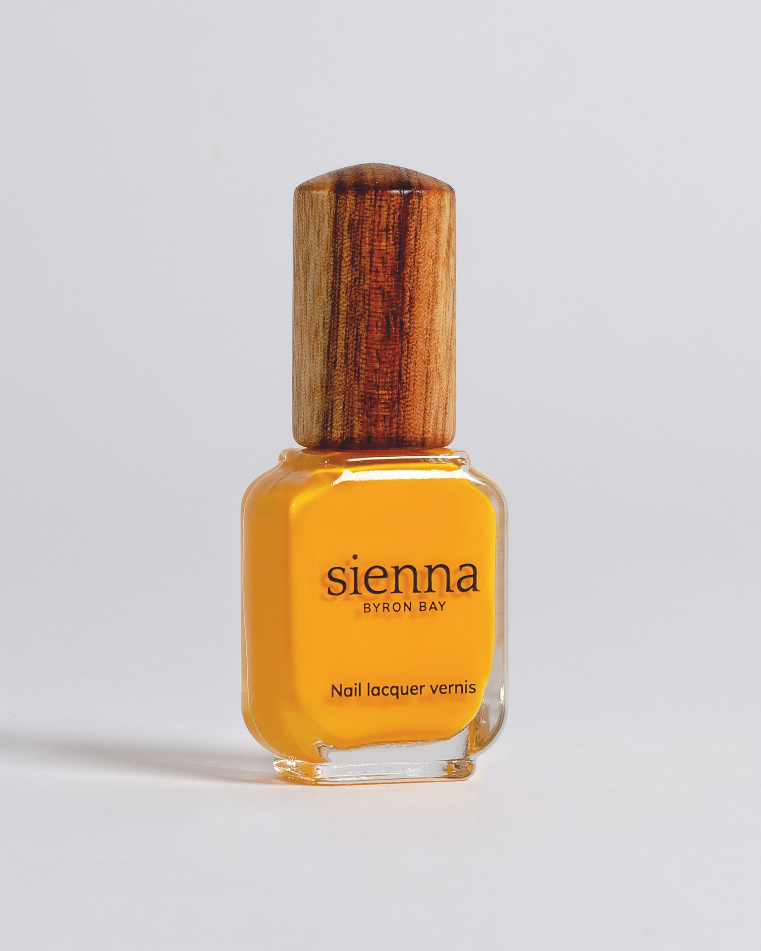 yellow nail polish bottle with timber cap by sienna