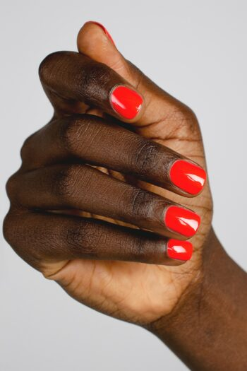 Warm red nail polish hand swatch on dark skin tone by sienna