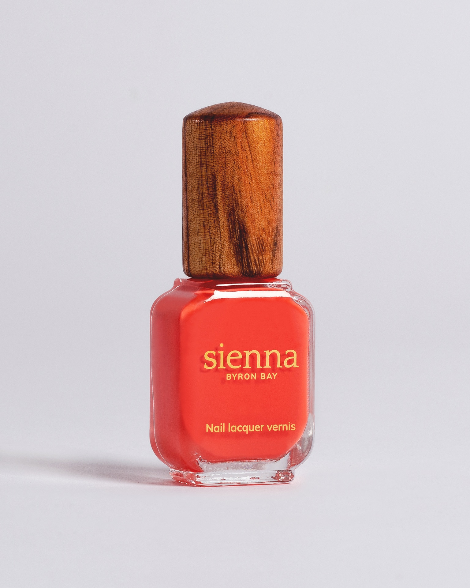 warm red nail polish bottle with timber cap by sienna
