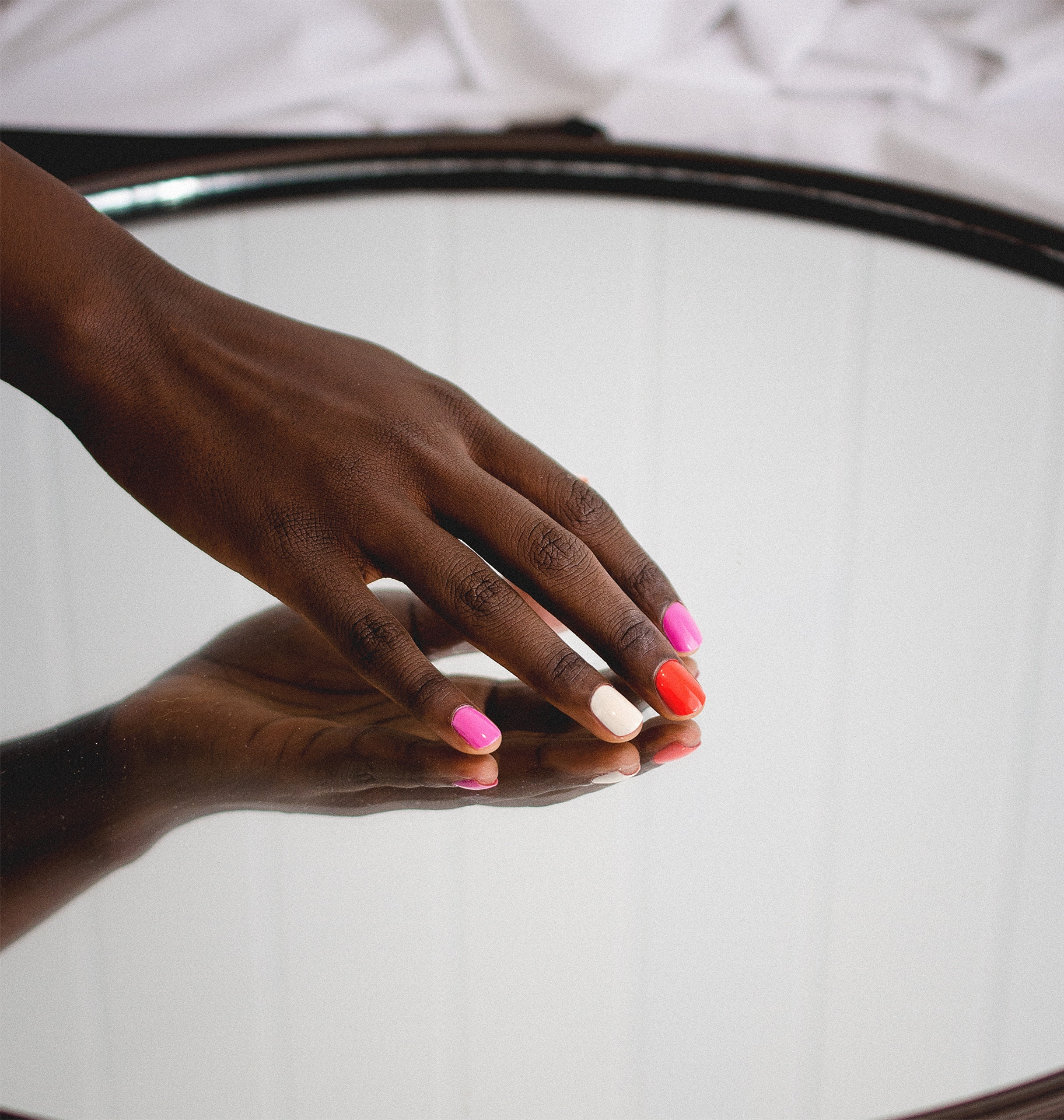 dark skin hand posed on a mirror wearing 3 different nail polishes by sienna