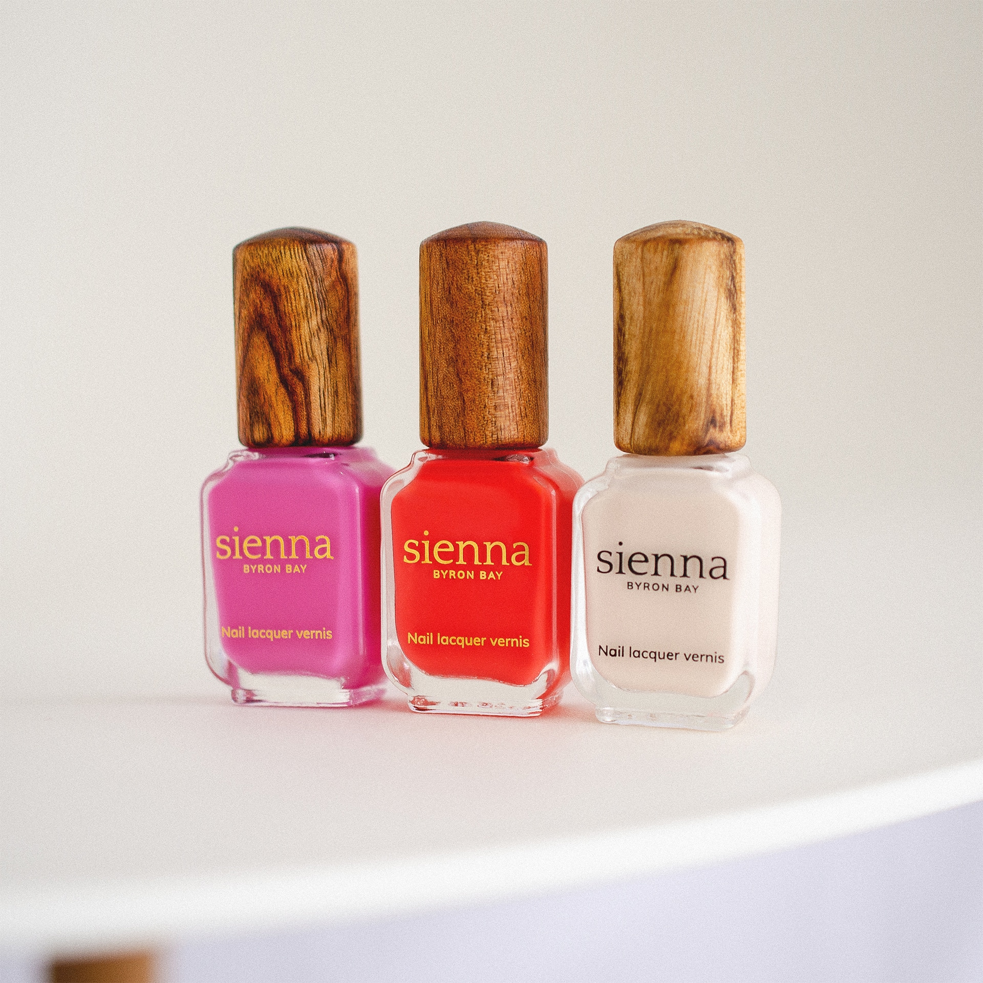 pink red and white nail polish next to each other on a white background by sienna