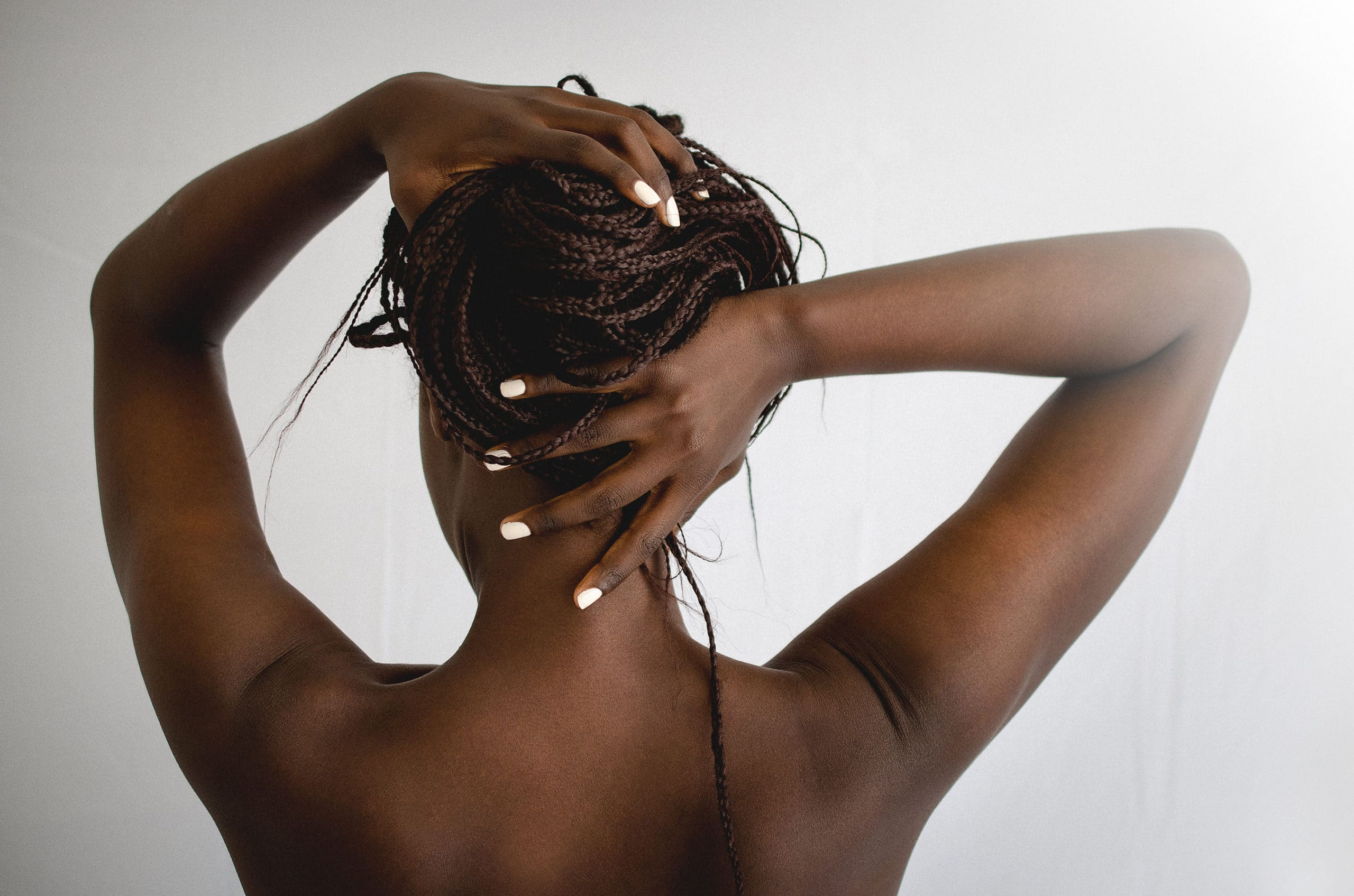 dark skin model seen from the back holding her braids wearing white nail polish by sienna