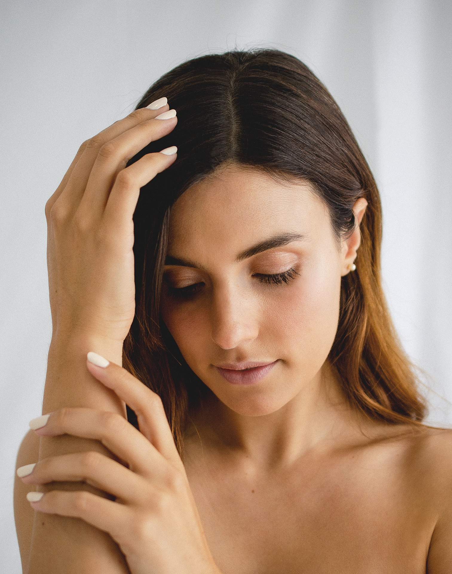 young woman holding her hands to her head, wearing white nail polish by sienna