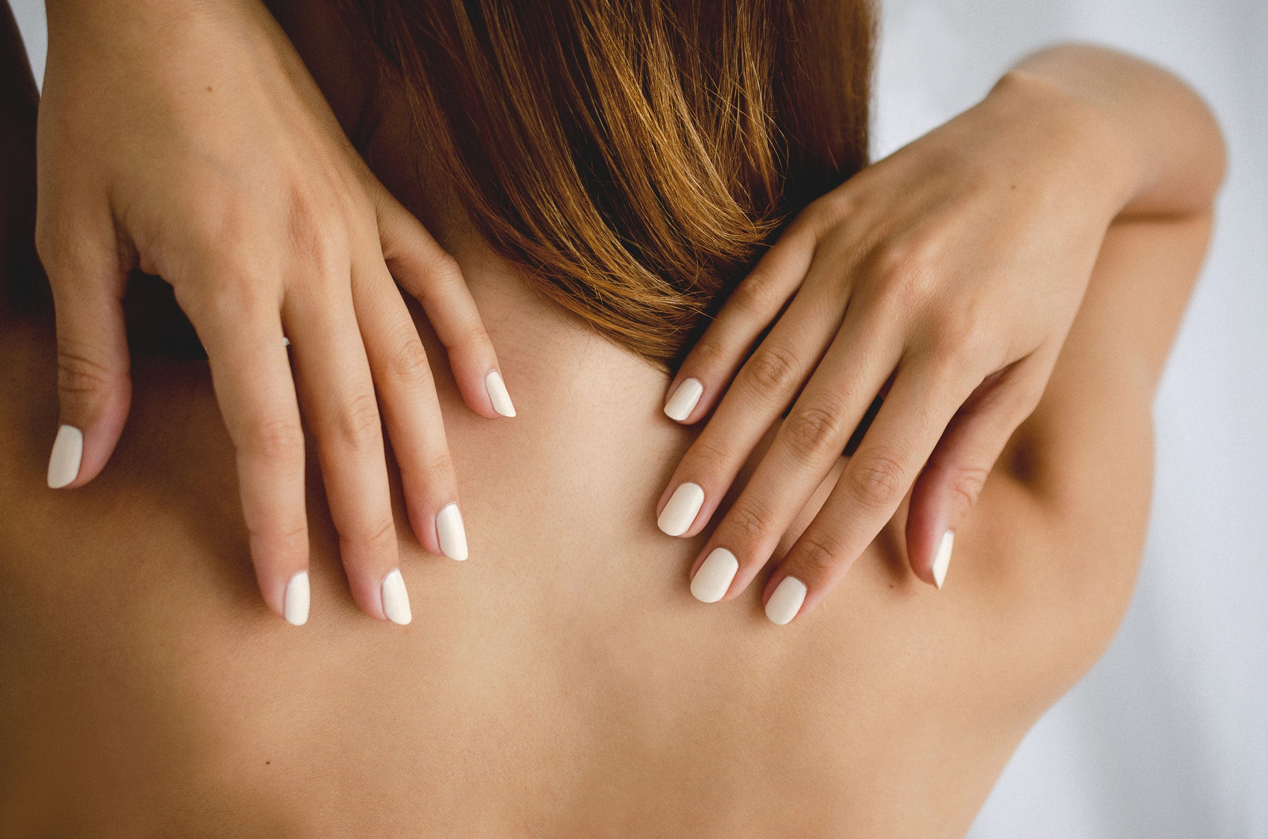 close up of the naked back of a fair skin model with her hands on her back wearing white nail polish by sienna