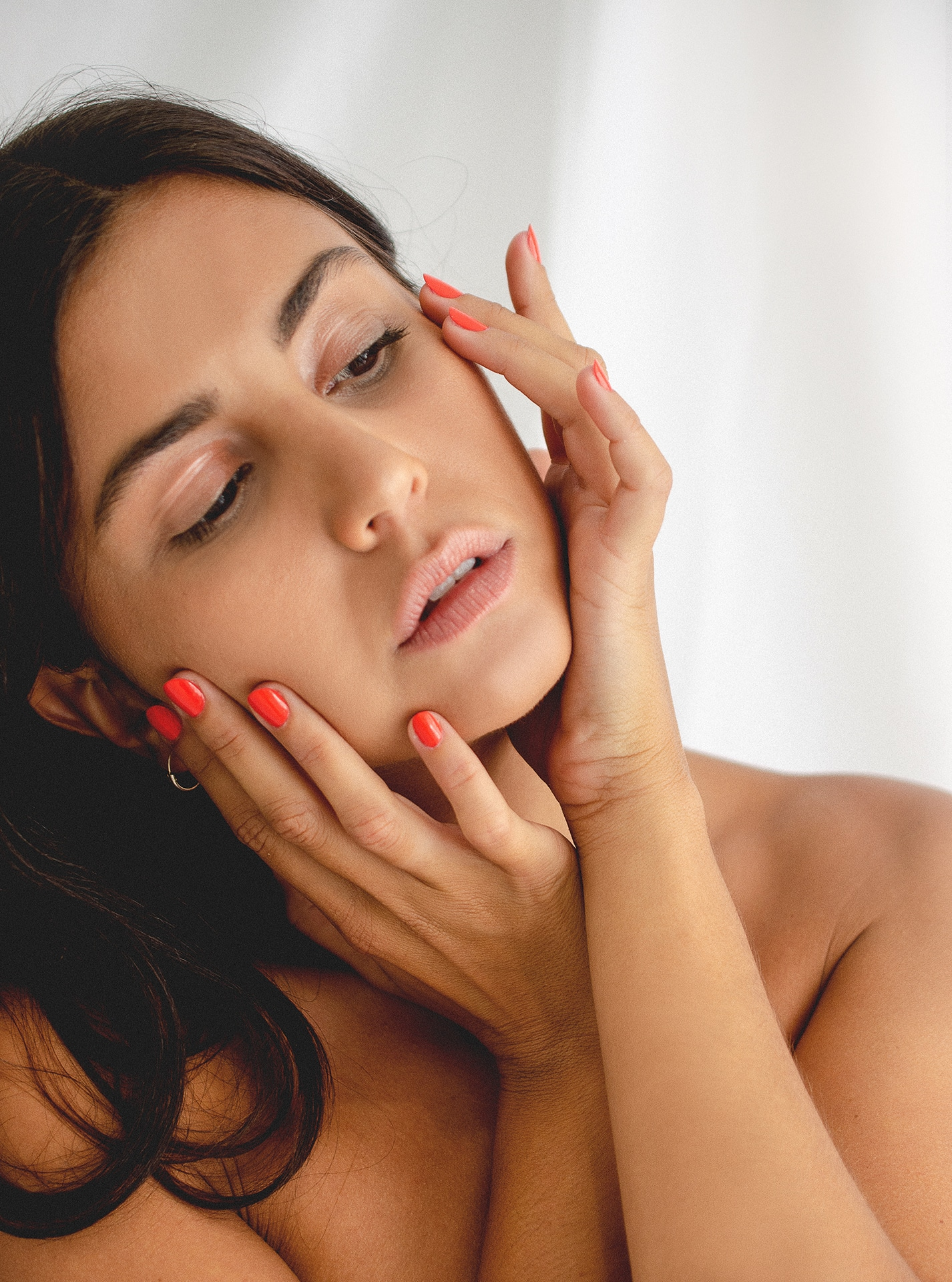 olive skin model holding her hand to her face wearing red nail polish by sienna