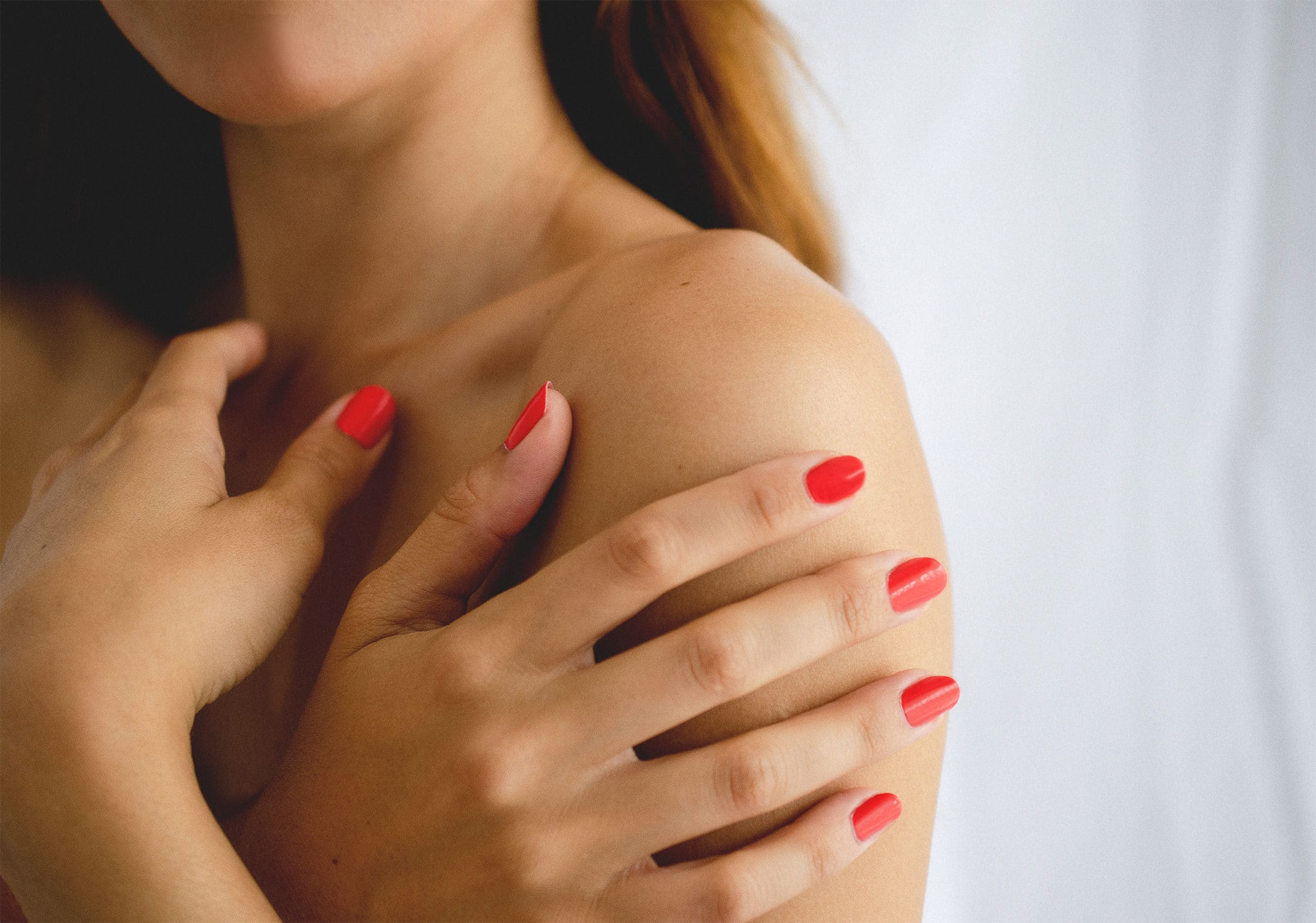 young woman holding her hands to her shoulder wearing red nail polish by sienna