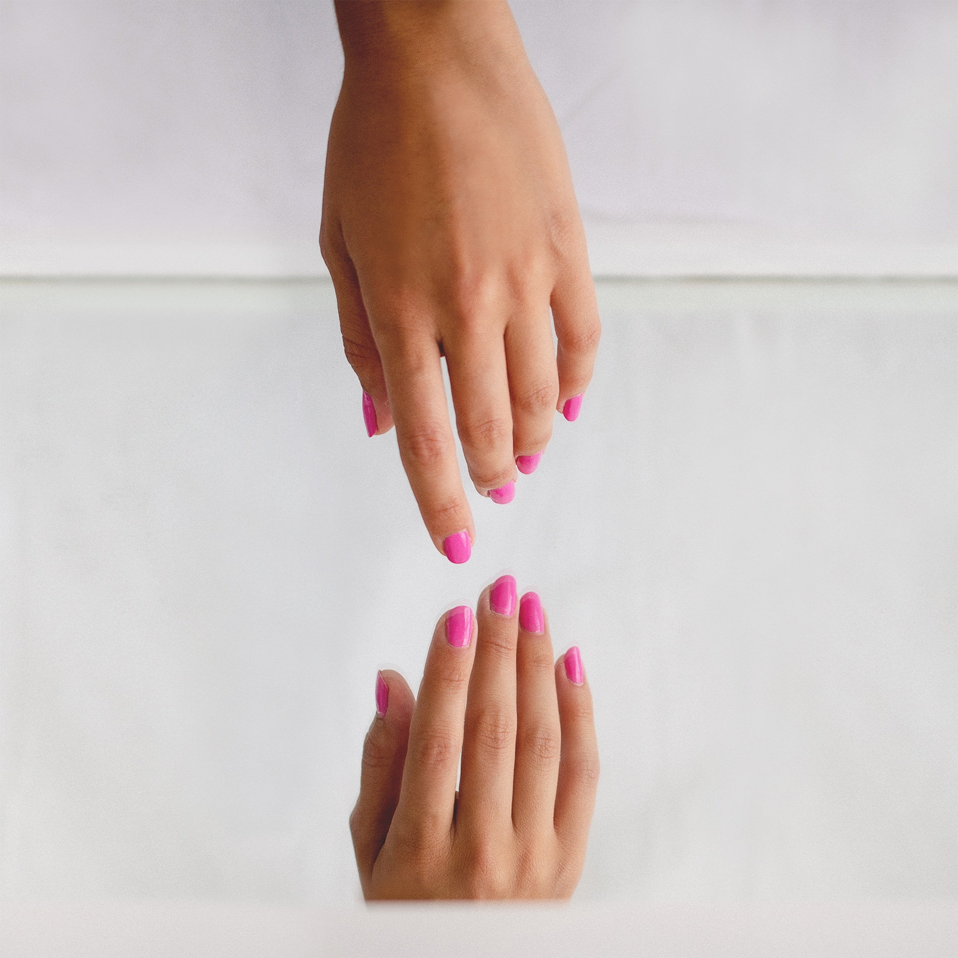 hand on mirror with pink nail polish by sienna