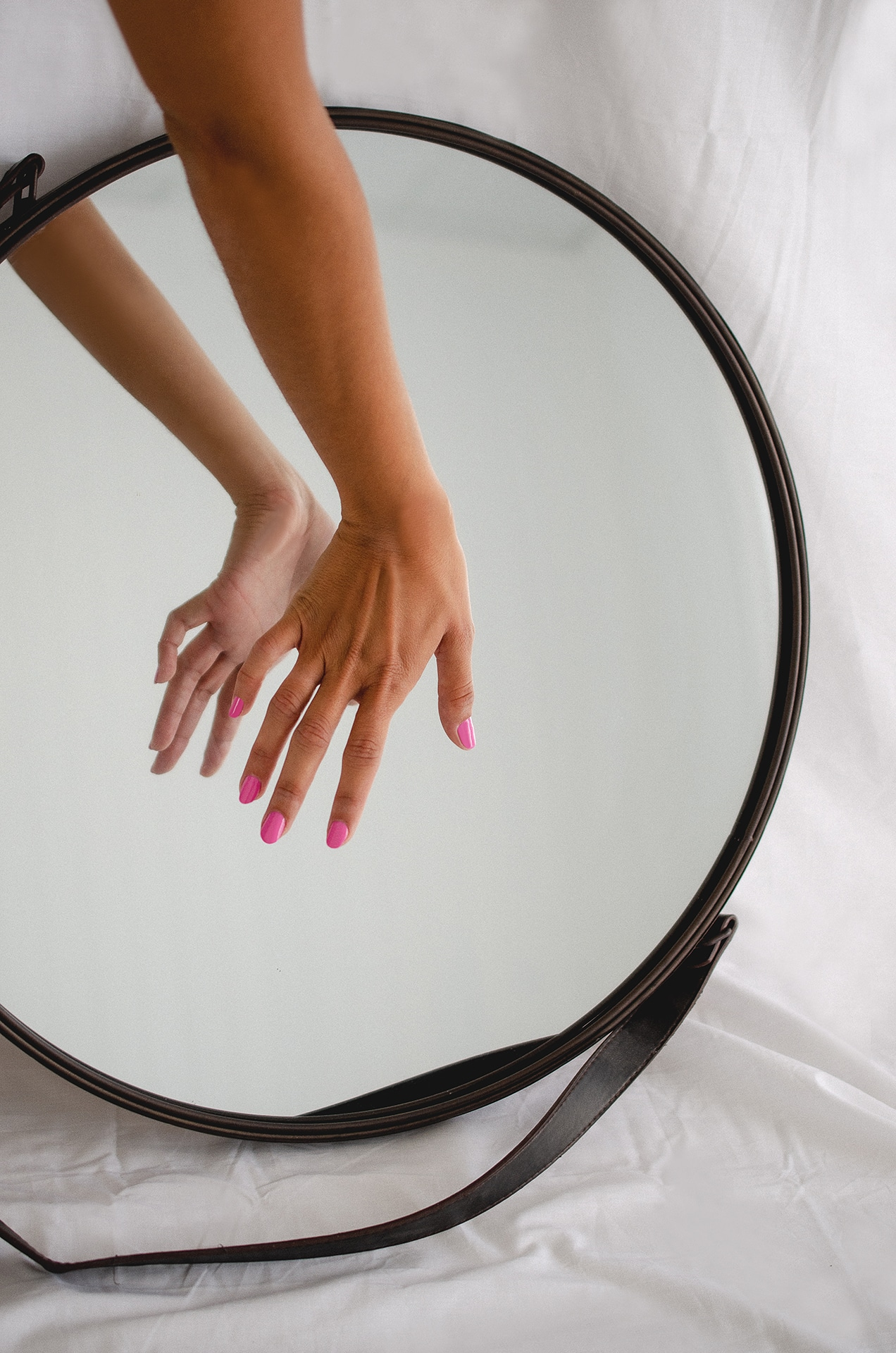 hand in front on mirror wearing pink nail polish by sienna