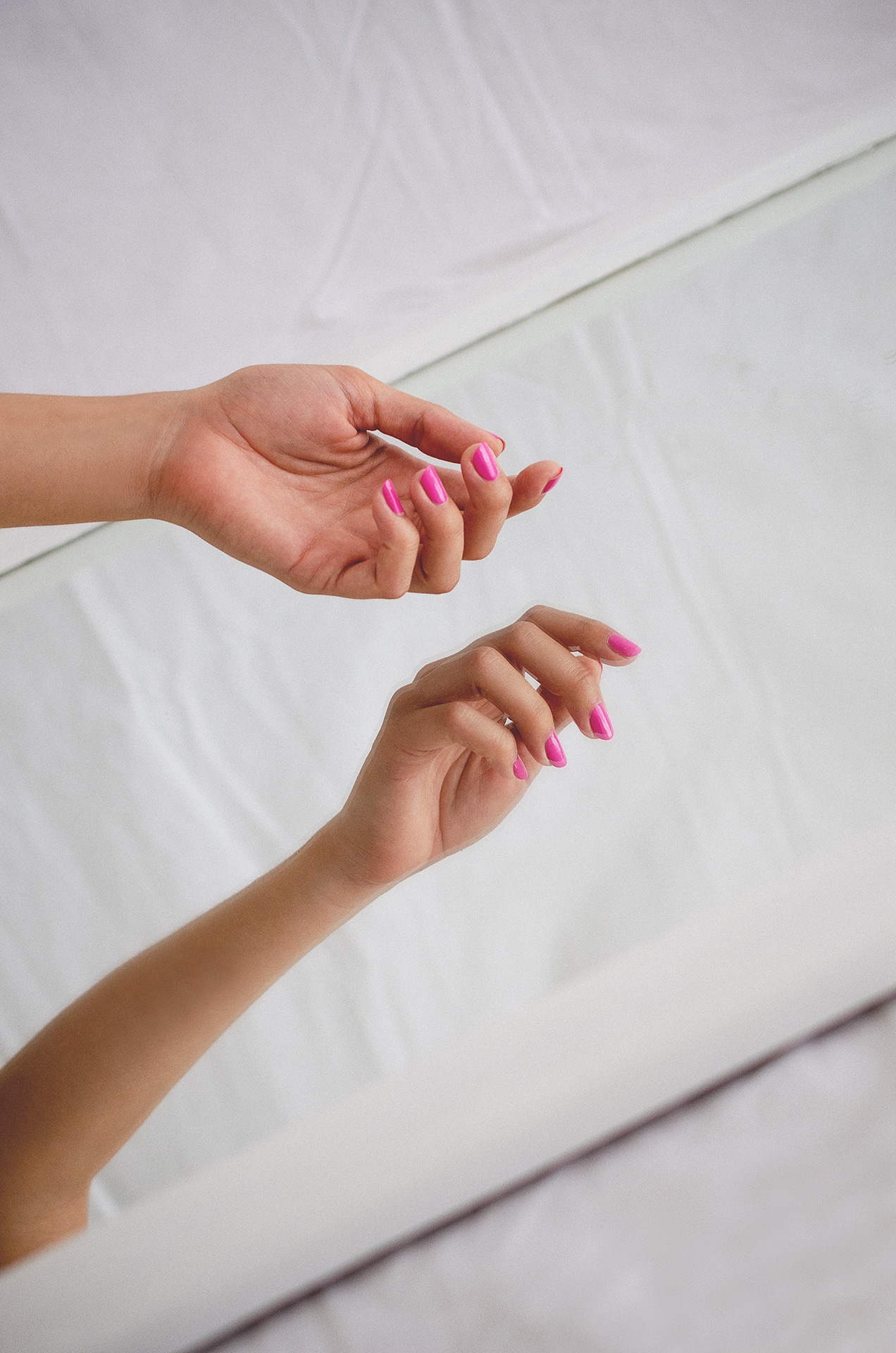 fair skin model wearing pink nail polish by sienna holding her hand over a mirror
