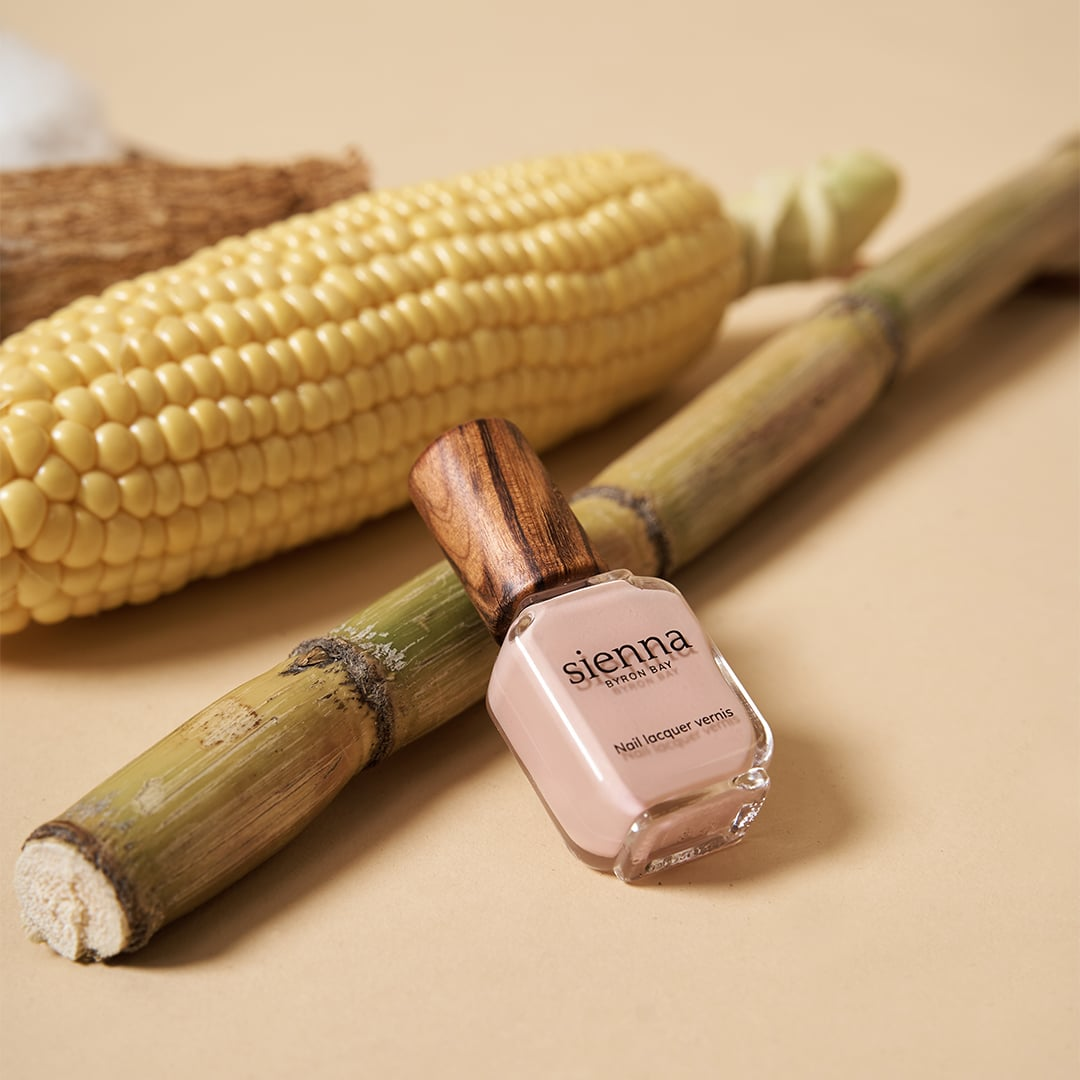 light pink nail polish bottle by sienna on sugar cane with corn and cassava on beige background