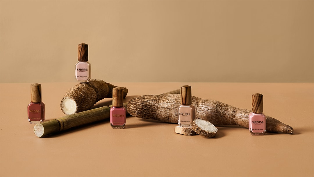 pink nail polish bottles by sienna on beige background with sugar cane and cassava