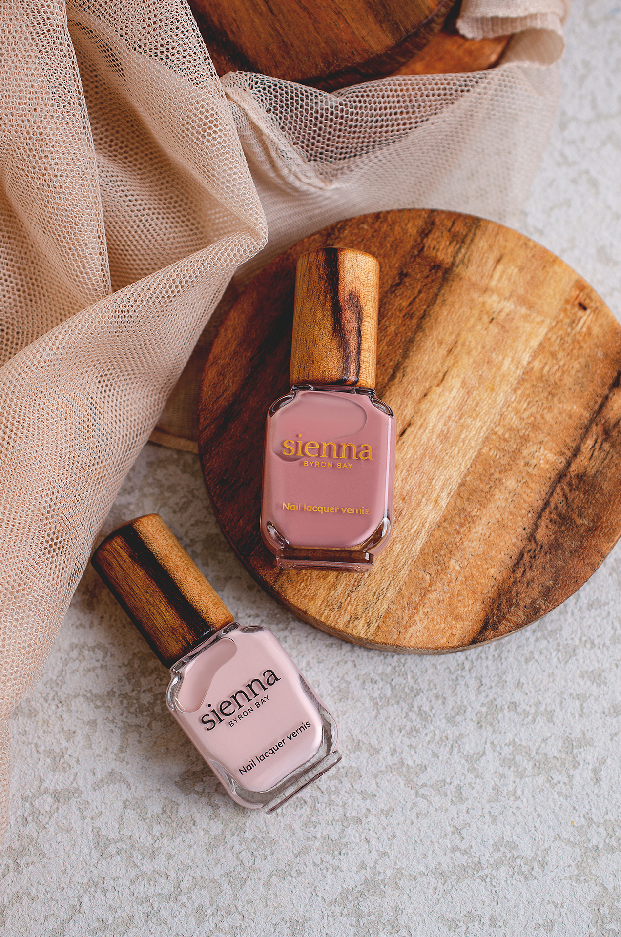 top shot of dusty light and mid-tone pink nail polish bottles with timber cap on timber coaster and concrete background by sienna
