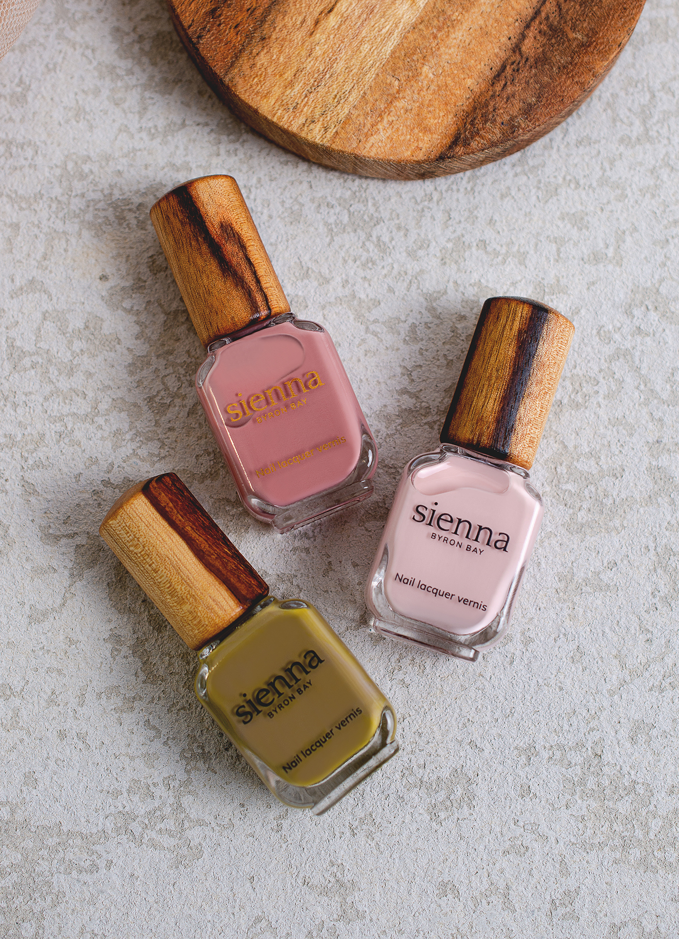 top shot of kaki green pink and pastel nail polish bottles with timber cap by sienna on concrete background